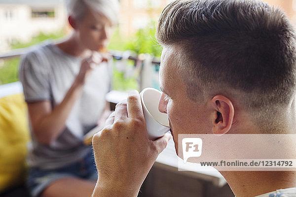 Man drinking coffee on balcony