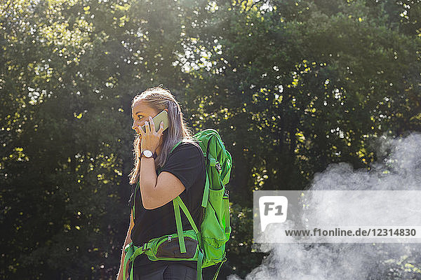 Young woman talking on phone in meadow