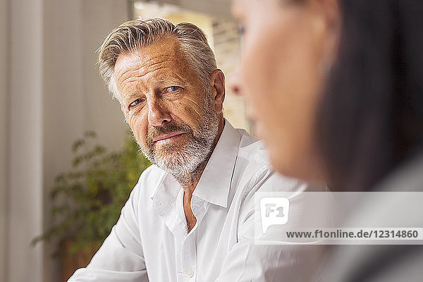 Senior man and mature woman talking in cafe