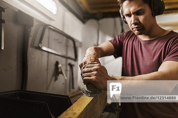 Man polishing wood in garage
