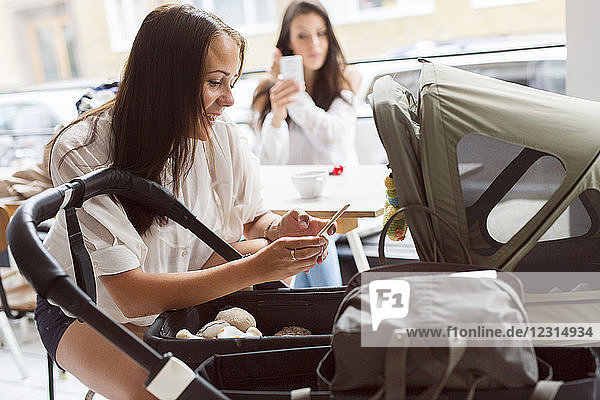 Two young women with baby stroller in cafe