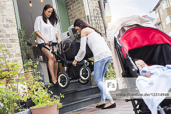 Two young women carrying stroller with baby boy (6-11 months)