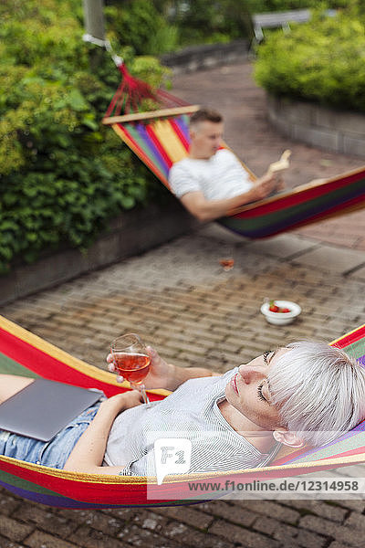 Couple relaxing on hammocks