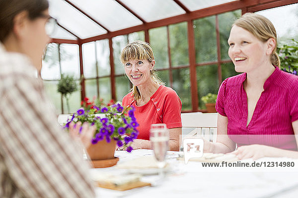 People talking at table in conservatory