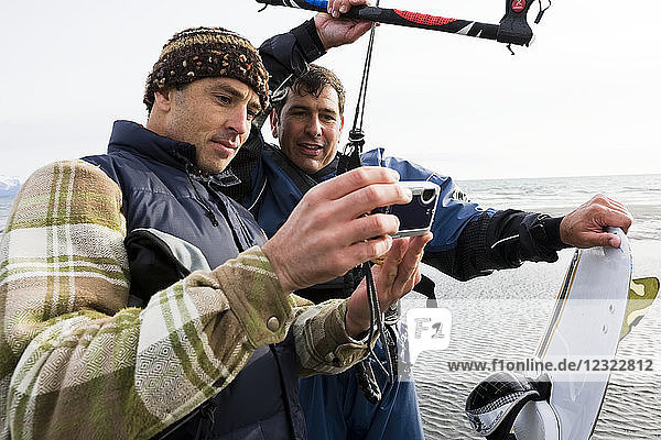 Two men review photos on a camera during a kitesurfing class  Kachemak Bay  South-central Alaska; Alaska  United States of America