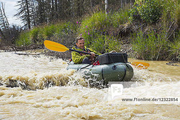 A man pack rafting on Jarvis Creek floats over a submerged log  Interior Alaska; Alaska  United States of America