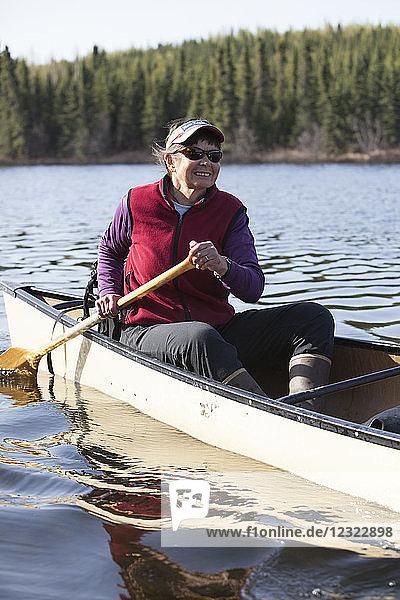 Woman steering a canoe in the Swanson Lake area  Kenai Peninsula  South-central Alaska; Alaska  United States of America