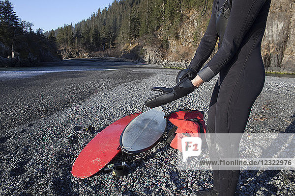 Female surfer gears up on the beach before surfing in the Gulf of Alaska  South-central Alaska; Alaska  United States of America