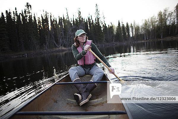 Woman in a canoe at Swanson Lake  Kenai Peninsula  South-central Alaska; Alaska  United States of America