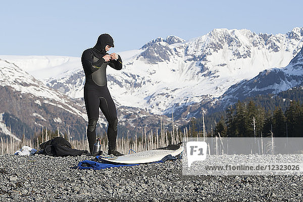 Surfer gearing up to go surfing on the Kenai Peninsula Outer Coast  South-central Alaska; Alaska  United States of America