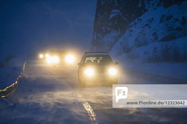 Car headlights from traffic illuminate the blowing snow on the Seward Highway during a dark winter night  Kenai Peninsula  Turnagain Arm  South-central Alaska; Alaska  United States of America