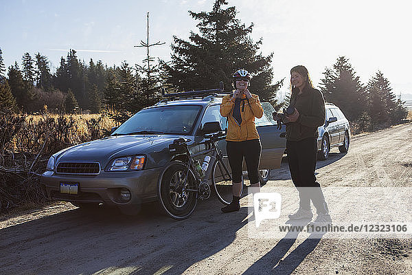 Two women preparing for a bike ride near Homer  Kenai Peninsula  South-central Alaska; Alaska  United States of America