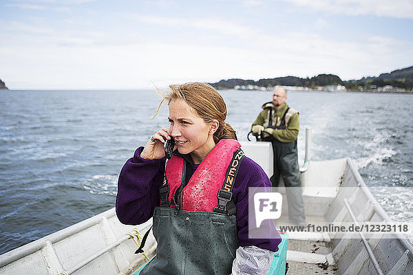 Set-netter talking on a cell phone while her husband drives a set-net skiff in Seldovia Bay  South-central Alaska; Alaska  United States of America