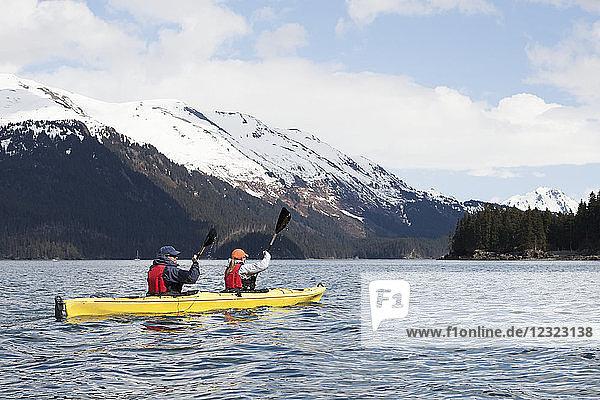 Two sea kayakers in a double sea kayak  Kachemak Bay  Southcentral Alaska; Alaska  United States of America