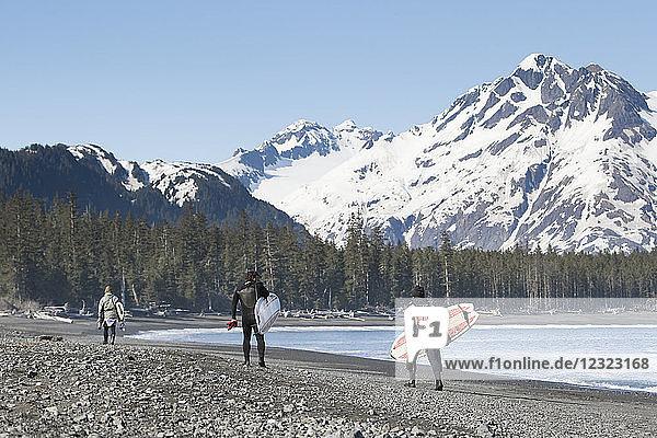 Surfers walking on the beach along the Kenai Peninsula Outer Coast  South-central Alaska  USA