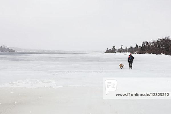 Man with a dog on a freshwater Harbour Seal hunt  Lake Iliamna  Pedro Bay; Southwestern Alaska; Alaska  United States of America