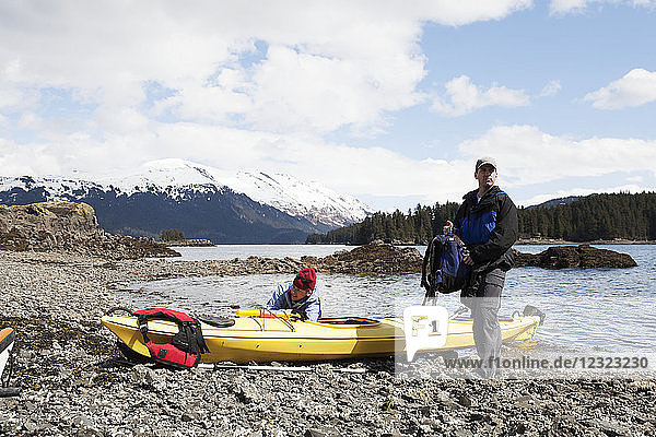 Two sea kayakers on shore with their boat  Kachemak Bay  South-central Alaska; Alaska  United States of America