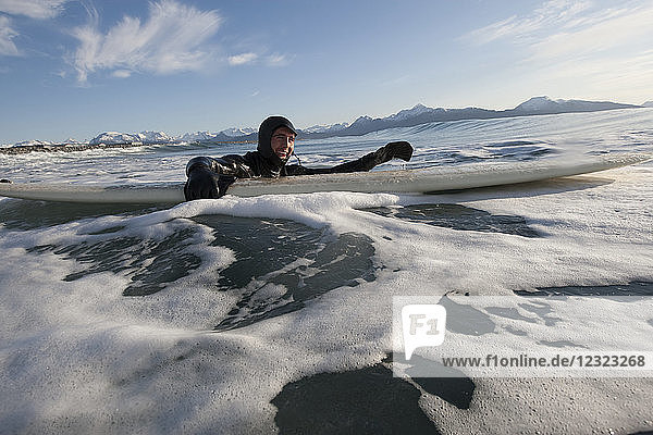 Man swimming with his surfboard  South-central Alaska; Homer  Alaska  United States of America