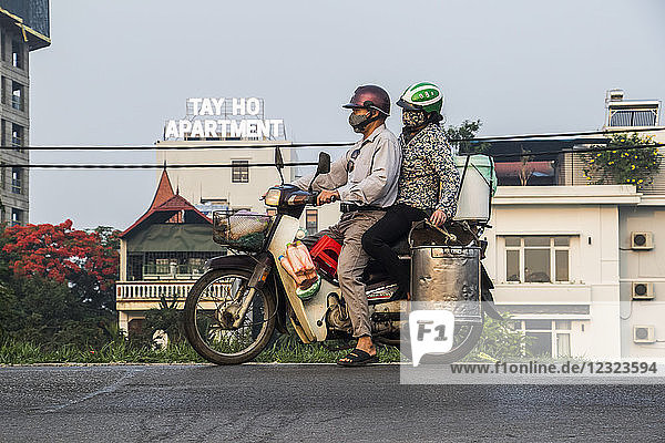 Couple riding a motorcycle laden with containers in the Old Quarter; Hanoi  Vietnam