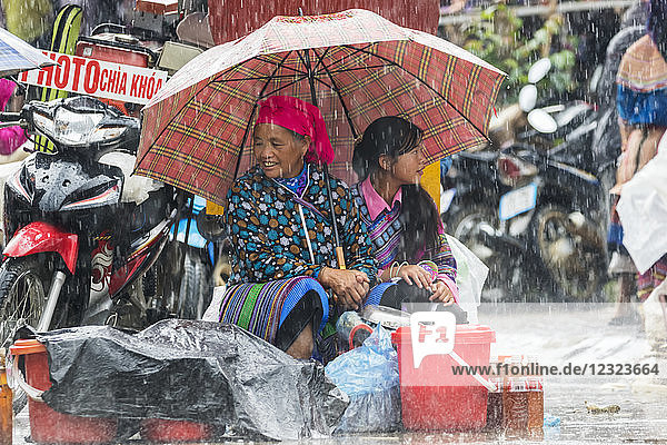 Hmong women at the Sunday market in the rain; Bac Ha  Lao Cai  Vietnam