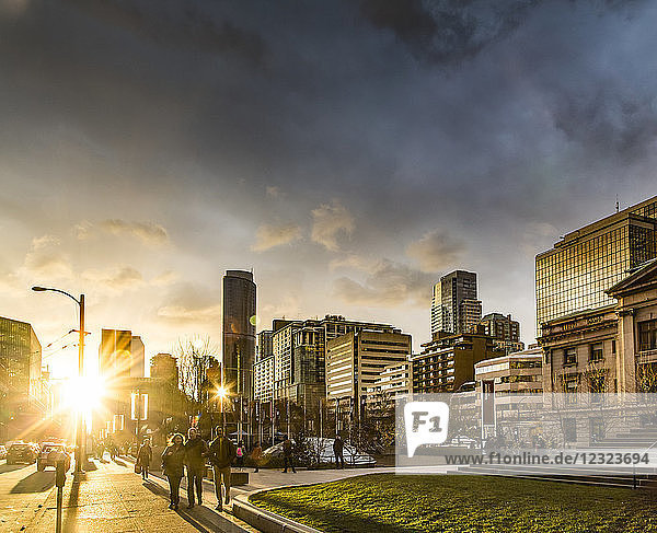 A street scene in Vancouver at sunset with pedestrians and buildings reflecting sunlight; Vancouver  British Columbia  Canada