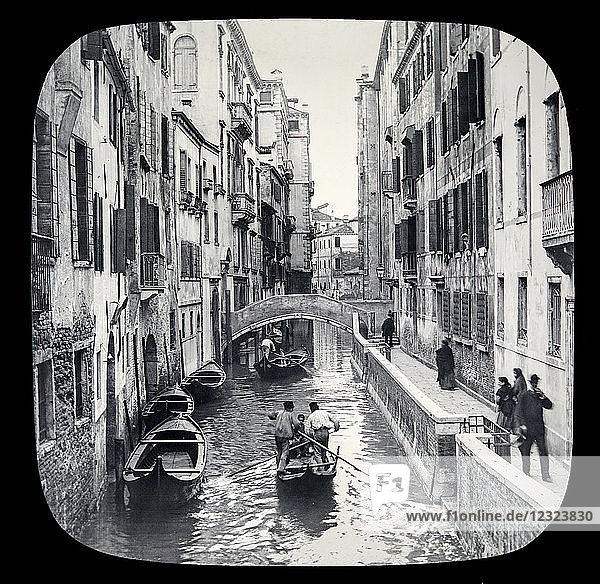 Magic lantern slide circa 1900.Victorian/Edwardian.Social History. The Beauties of Venice photographs created in 1888 Joseph John William ACWORTH F.I.C.  F.C.S.J. The Beauties of Venice . Canal Scene  instantaneous. There are no fewer than 150 canals intercepting Venice in various directions; these canals being connected by 378 bridges of more or less artistic design  and generally built of stone or marble. Most of the houses rise immediately from the canals  sometimes they are separated from them by a narrow street  or ' calle '' such as we see in the view before us  these streets being paved with broad slabs of stone  sometimes with brick or asphalte [B] The view being instantaneous gives us a good idea of the life pervading the city  which is now becoming one of the greatest seaports of the Adriatic.