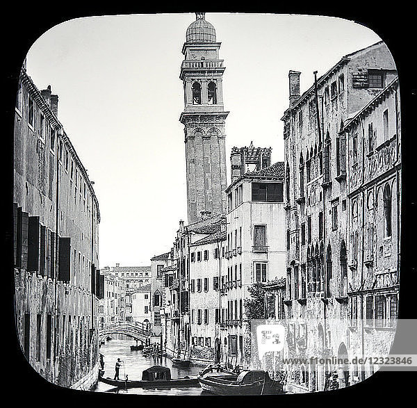 Magic lantern slide circa 1900.Victorian/Edwardian.Social History. The Beauties of Venice photographs created in 1888 Joseph John William ACWORTH F.I.C.  F.C.S.J. The Beauties of Venice. Re-entering the Grand Canal  passing onwards towards the Arsenal  and looking up one of the canals on our left  we get the present interesting picture  so thoroughly Venetian in character. One peculiarity is the leaning Campanile  or Bell-tower  which we notice in the centre of the view. The tower certainly looks dangerous ; however  as the centre of gravity yet lies within the base  it is still considered quite safe from falling over. There are many leaning towers all over Italy  the one at Pisa being the most celebrated [B] but whether they are produced accidentally or purposely does not appear to have been decided.