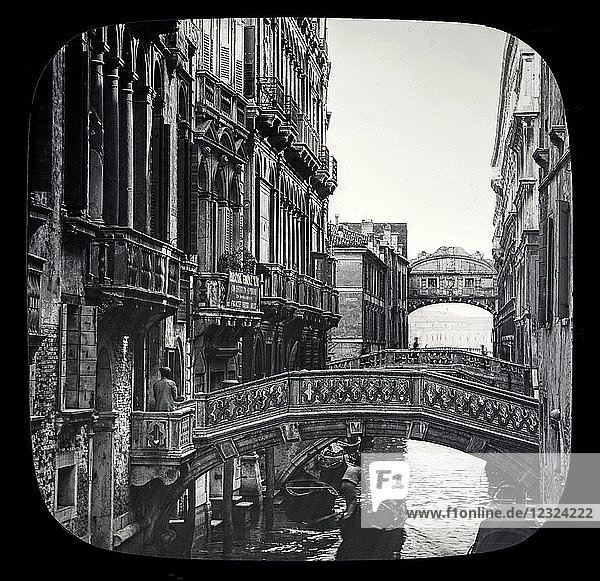 Magic lantern slide circa 1900.Victorian/Edwardian.Social History. The Beauties of Venice photographs created in 1888 Joseph John William ACWORTH F.I.C.  F.C.S.J. The Beauties of Venice . Along the Canal leading to Bridge of Sighs. This view shows us a series of those ornate marble bridges spanning the Palace Canal  and connecting the various 'calli ' or narrow streets  on both sides of it. Right and left we get a good idea of the style of architecture of a large proportion of the habitations of Venice. They are substantially built  and for the most part when Venice was enjoying more fortunate times. ·' Those days are gone  but beauty still is here' [B] In the distance we see the other side of the Bridge of Sighs and the open lagune beyond.