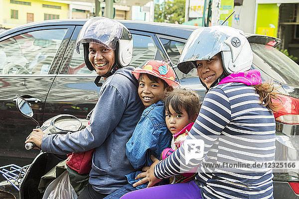 Family riding a motorcycle; Phnom Penh  Cambodia