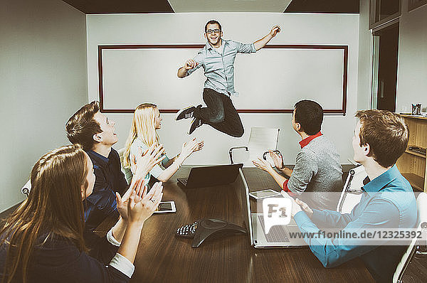 Young millennial business professional jumping to celebrate an accomplishment with his co-workers working in a conference room during a presentation and one of his piers taking a picture with a pad; Sherwood Park  Alberta  Canada