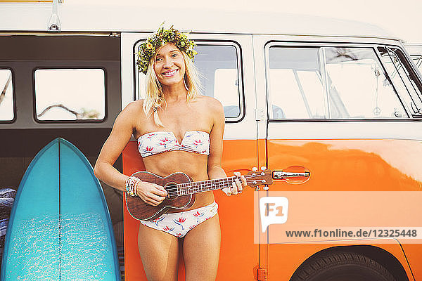 Beach Lifestyle  Beautiful Surfer Girl With Ukulele And Classic Vintage Surf Van On The Beach At Sunset