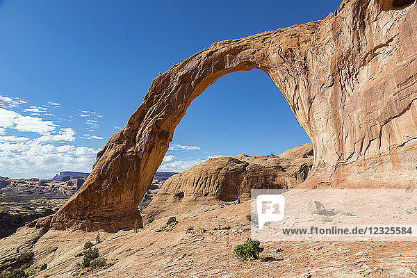A female hiker sitting under the towering Corona Arch; Moab  Utah  United States of America