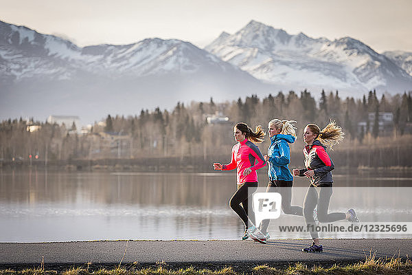 Three young women running on a trail along the water's edge with mountains in the distance; Anchorage  Alaska  United States of America