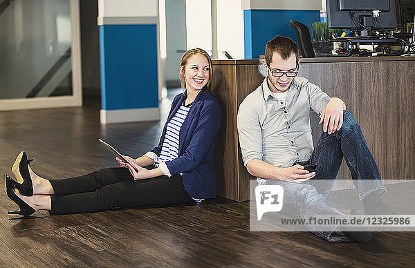 Two young millennial professionals taking a break and sitting on the floor of their workplace using technology; Sherwood Park  Alberta  Canada