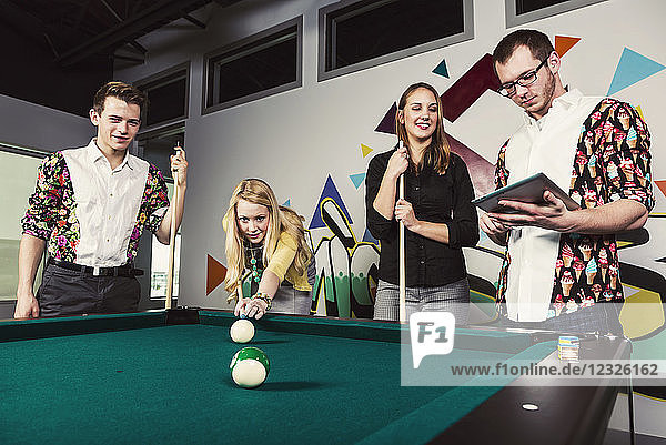 A group of young millennial business professionals playing a game of pool together on a work break; Sherwood Park  Alberta  Canada