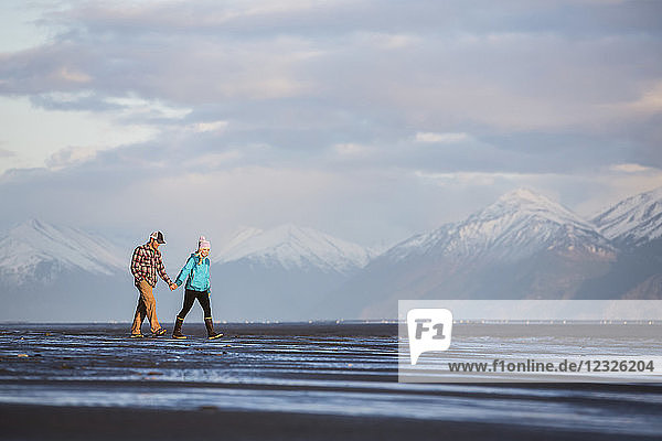 A young couple walking on a beach and holding hands with a mountain range in the distance; Anchorage  Alaska  United States of America