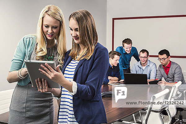 Two young millennial business professionals looking at a tablet while working together in a conference room with their peers; Sherwood Park  Alberta  Canada
