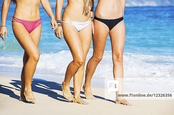 Group Of Friends Walking On Tropical Beach. Close Up On Legs And Bikinis
