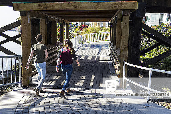 Two young women walk together down a path under a bridge in a park; New Westminster  British Columbia  Canada