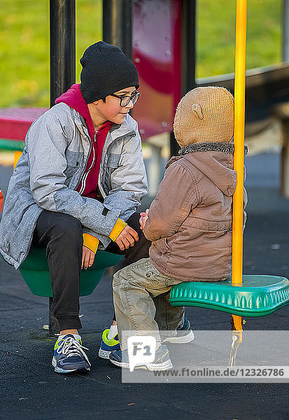 A young boy with his older brother sitting and talking at a playground; Langley  British Columbia  Canada