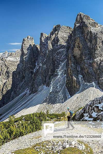 Female hiker on trail with valley below against a rugged mountain range and blue sky; Sesto  Bolzano  Italy