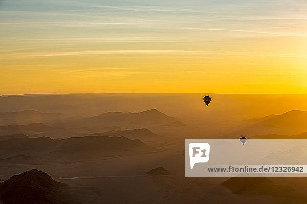 Silhouette of hot air balloons in the golden sky over the sand dunes at sunrise in the Namib Desert; Sossusvlei  Hardap Region  Namibia