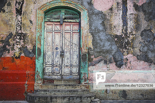 Worn and weathered facade of a building with peeling paint and double doors; Nicaragua