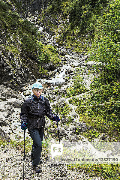 Female hiker on steep trail with rocky creek in the valley below; Grainau  Bavaria  Germany