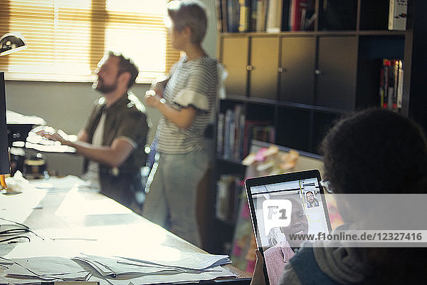 Creative businessman video chatting with colleague on digital tablet in office