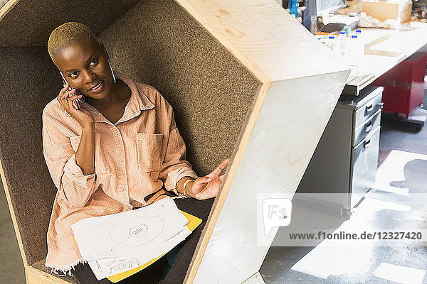 Creative businesswoman talking on smart phone in cubby