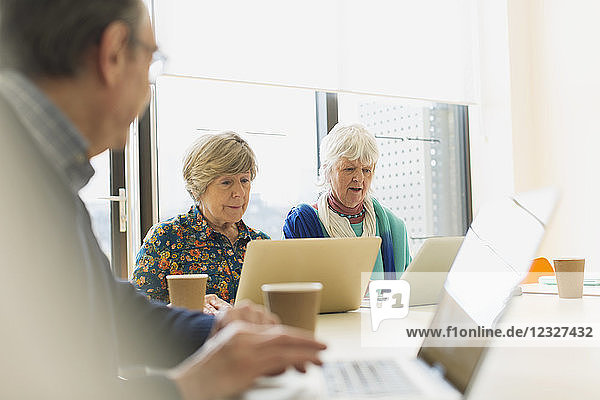 Senior businesswomen using laptops in conference room meeting