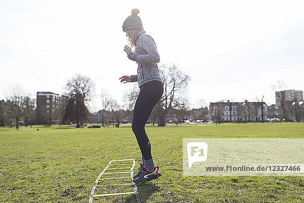 Woman practicing speed ladder drill in sunny park