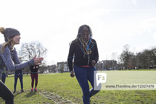 Smiling woman doing speed ladder drill in sunny park