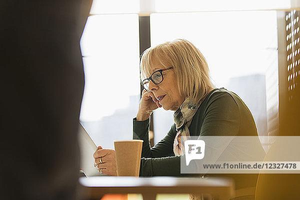 Focused senior businesswoman using digital tablet